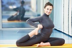 体操健身执行的愉快的微笑的妇女 免版税库存图片