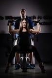 体操培训重量妇女 做引体向上的妇女行使举的哑铃 免版税库存图片