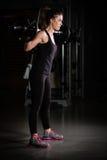 体操培训重量妇女 虔诚在健身房和做蹲坐低调照片的车身制造厂女孩举的重量 免版税库存照片