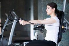体操培训重量妇女 行使拉下重量机器 做引体向上的妇女行使举的哑铃 图库摄影