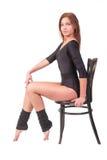 体操服的可爱的妇女坐椅子 库存图片