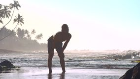 体操运动员在浅水区站立用在膝盖的手 股票视频