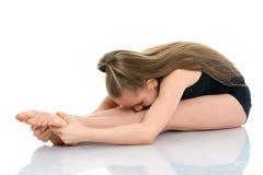 体操运动员执行在地板上的一个杂技元素 免版税库存图片