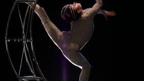 体操运动员a在垂直的串的金属结构月亮转动 黑色背景 慢的行动 股票录像