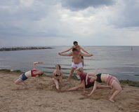 体操金字塔 青年在海滩的趣味游戏 库存照片