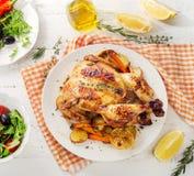 整体烤了与菜和沙拉的鸡在木后面 免版税库存照片