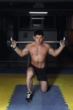 体育、体型、生活方式和人概念-有屈曲肌肉和做肩膀在健身房的杠铃的年轻人新闻刺 库存图片