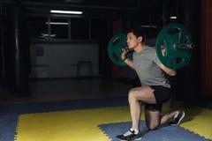体育、体型、生活方式和人概念-有屈曲肌肉和做肩膀在健身房的杠铃的年轻人新闻刺 库存照片