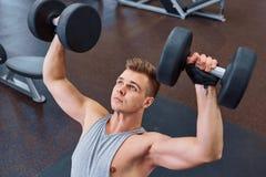 体育、体型、训练和人概念-有屈曲肌肉的哑铃的年轻人 人与哑铃一起使用他的身体在 库存图片