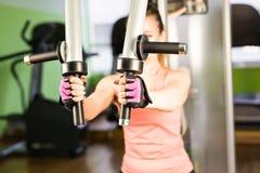 体育、健身、体型、配合和人概念-屈曲在健身房机器的少妇肌肉 免版税图库摄影