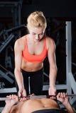 体育、健身、配合、举重和人概念-女孩个人教练员与人杠铃一起使用 库存图片