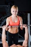 体育、健身、配合、举重和人概念-女孩个人教练员与人杠铃一起使用 图库摄影