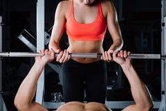 体育、健身、配合、举重和人概念-女孩个人教练员与人杠铃一起使用 库存照片