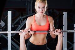体育、健身、配合、举重和人概念-女孩个人教练员与人杠铃一起使用 免版税库存照片