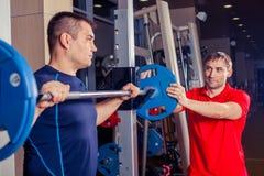 体育、健身、配合、建身的人概念-人和与屈曲在健身房的杠铃的个人教练员肌肉 免版税库存照片