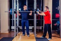 体育、健身、配合、建身的人概念-人和与屈曲在健身房的杠铃的个人教练员肌肉 免版税库存图片