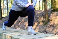 体育伤害 充满痛苦的妇女在膝盖,当跑步时 图库摄影
