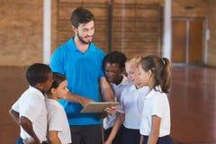 体育使用数字式片剂的老师和学校孩子在篮球场 库存照片