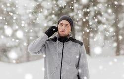 体育供以人员与耳机在冬天森林里 库存图片