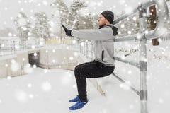 体育供以人员做蹲坐在篱芭在冬天 免版税图库摄影