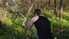 体育供以人员训练与波浪起伏的绳索 Hardwork 黑色衬衣t 有树的绿色公园 sunnyday 后侧方视图 股票视频
