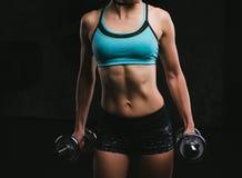 体育健身在黑暗的背景的妇女训练 美好的机体 库存图片