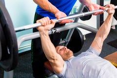 体育健身房训练的人与杠铃 免版税库存照片