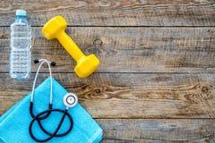 体育和健康 健身 哑铃和听诊器在木背景顶视图copyspace 免版税库存照片