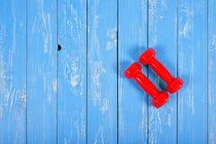 体育和健身-两个红色哑铃木背景 库存照片