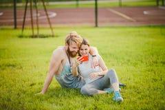 体育和技术 在休息在锻炼以后的爱异性爱白种人夫妇的年轻人户外在草坪的公园,绿色 免版税图库摄影