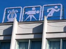体育和文化的三个减速火箭的标志在都市大厦屋顶 库存照片
