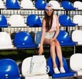 体育和时尚 有摆在为在时髦夏天成套装备的体育场位子和颜色的腿长的秀丽的一个狂热爱国者的  免版税库存图片