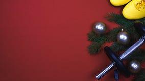 体育圣诞节成套工具:红色哑铃、黄色圣诞树运动鞋和分支与装饰品的在红色背景 免版税库存图片