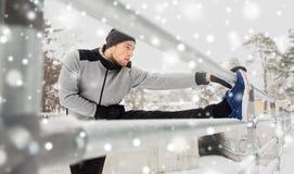 体育在冬天供以人员舒展腿在篱芭 库存图片