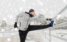 体育在冬天供以人员舒展腿在篱芭 免版税库存图片