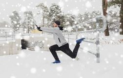 体育在冬天供以人员舒展腿在篱芭 免版税库存照片