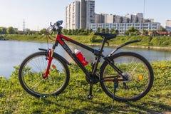 体育在绿草骑自行车在城市湖附近 库存图片