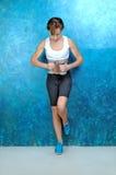 体育在蓝色墙壁附近的健身妇女 免版税库存照片