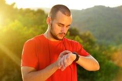 体育在锻炼以后供以人员检查在手表的时间 库存图片