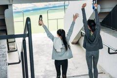 去体育场的运动服的两个愉快的女运动员 库存图片