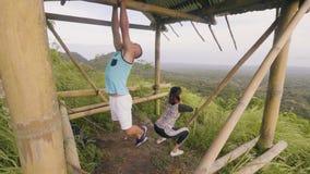 体育夫妇训练室外在青山和山风景 拔在单杠的体育人 亭亭玉立的妇女 影视素材