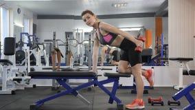 体育女孩在体育长凳泵浦倾斜前臂的肌肉,与哑铃的三头肌 Loopable 股票录像