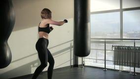 体育妇女参与拳击,训练与在健身俱乐部的拳击袋子 股票录像