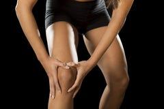 年轻体育妇女藏品伤害了在韧带伤害的膝盖遭受的痛苦或拉伤了肌肉 免版税库存照片