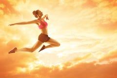 体育妇女赛跑,运动员女孩跳跃,愉快的健身概念 免版税库存图片