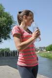 体育妇女饮用水和微笑 库存图片