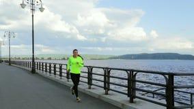 体育布料的白种人深色的妇女在堤防跑在河附近 股票录像