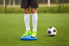 体育平衡训练 稳定在平衡坐垫的足球训练 库存图片