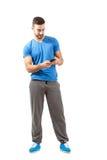 体育成套装备的年轻运动员使用巧妙的电话 库存图片