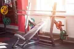 体育换下场与杠铃,并且在执行杠铃长凳的机架的圆盘压入现代健身房,肌组织,太阳 图库摄影
